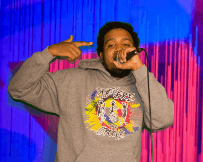 man in colorful hoodie singing into mic